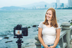 A young woman blogger leads her video blog in front of a camera by the sea. Blogger concept Royalty Free Stock Images