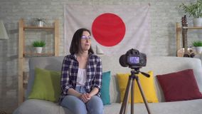 Young woman blogger in the shirt on the background of the flag of Japan records a video. Young woman blogger in shirt and glasses on the background of the flag stock video