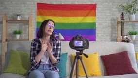 Young woman blogger in the shirt on the background of the flag of the LGBT records video. Young woman blogger in the shirt and glasses on the background of the stock video footage