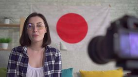 Young woman blogger in the shirt on the background of the flag of Japan records a video close up. Young woman blogger in shirt and glasses on the background of stock video