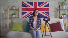 Young woman blogger in shirt on the background flag United Kingdom recording video. Young woman blogger in shirt and glasses on the background flag United stock video
