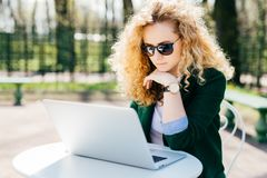 Young woman with blond curly hair wearing sunglasses and elegant green jacket sitting in front of open laptop outdoors reading new royalty free stock images