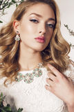 Young woman with blond curly hair wears elegant lace dress and bijou Stock Photo