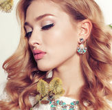 Young woman with blond curly hair wears elegant lace dress and bijou Stock Photos