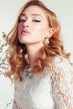 Young woman with blond curly hair wears elegant lace dress and bijou Stock Images