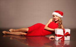 Young woman with blond curly hair wears Santa hat and elegant red dress Stock Photo