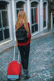Young woman with blond dreadlocks is on the pavement with a red suitcase. Royalty Free Stock Photography