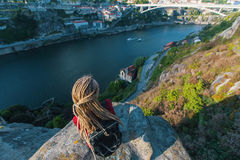 Young woman with blond dreadlocks sitting on a high cliff above the river. Travel. Stock Photo