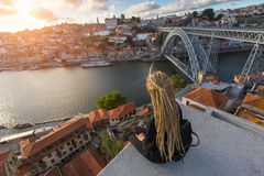 Young woman with blond dreadlocks sitting on viewpoint in front of Douro river and Dom luis I bridge in Porto Stock Photo