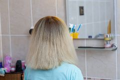 Young woman with blond hair combing her hair at home in the bathroom royalty free stock images