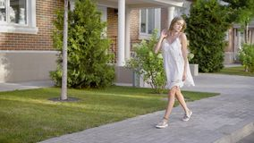 A young woman with blond hair dressed in a white designer dress elegantly walks down the street during the day stock video footage