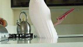 The woman in the kitchen uses the tablet, just woke up. Breakfast. Early morning. A young woman with blond hair and a pink shirt is standing in a dark kitchen stock video