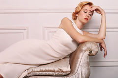 Young woman with blond hair in retro style,wears elegant white dress Royalty Free Stock Images