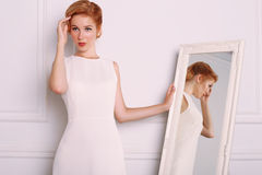 Young woman with blond hair in retro style,wears elegant white dress Stock Photography