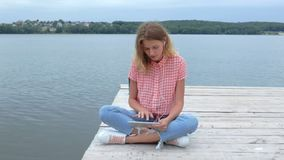 Woman tapping and waving at tablet near lake in slow motion stock video