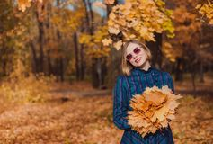 Young woman with blond hair wearing blue dress walking in autumn Park. Pretty tenderness model looking at camera. The girl in the hands of a bouquet of yellow royalty free stock photo