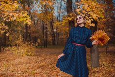 Young woman with blond hair wearing blue dress walking in autumn Park. stock photography