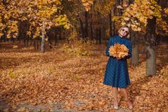 Young woman with blond hair wearing blue dress walking in autumn Park. royalty free stock photos