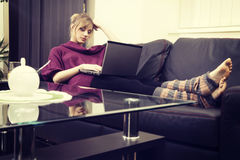 Young woman with blond hair working on her laptop at home Royalty Free Stock Images