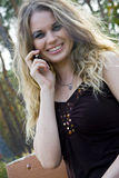 Young woman blonde on a background trees in a park.  Royalty Free Stock Photo