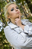 Young woman blonde on a background trees in a park.  Royalty Free Stock Photos