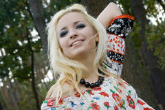 Young woman blonde on a background trees in a park.  Royalty Free Stock Images