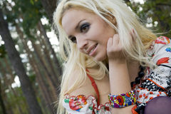Young woman blonde on a background trees in a park Stock Image