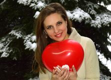 The young woman the blonde with blue eyes holds the red balloon in hand. It is a symbol of St. Valentine`s Day. The woman smiles Stock Photo