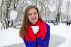 The young woman the blonde with blue eyes holds a snowball in the form of heart. The woman is dressed in a blue woolen sweater and red gloves and a scarf. The stock images