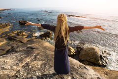 A young woman with blonde dreadlocks standing on the rocky shore of the ocean toward the sun. Stock Photos