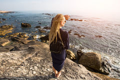 Young woman with blonde dreadlocks standing on the rocky shore of the ocean toward the sun. Stock Image