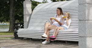 A young woman with a blonde girl rest in the park and eat hot corn. stock video