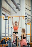Young woman with blonde hair hanging on the crossbar in the sports hall. Her trainer watching her. Young women with blonde hair hanging on the crossbar in the stock photo
