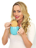 Young Woman With Blonde Hair Relaxing and Dunking a Biscuit in a Mug of Tea. Attractive Woman, with long blonde hair and in her twenties, holding a blue mug of Royalty Free Stock Photos