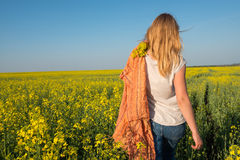 Young woman, blonde with orange scarf is walking through a field Royalty Free Stock Images