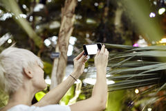 Young woman with blonde short hair is taking photo using phone camera. Empty space for layout. Focused on phone Stock Photography