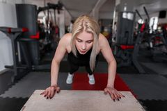 Young woman blonde in sporty black clothes is training in the gym. Girl does exercises for hands in fitness studio. royalty free stock photos