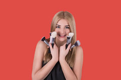 The young woman the blonde with various brushes for a make-up Royalty Free Stock Photography