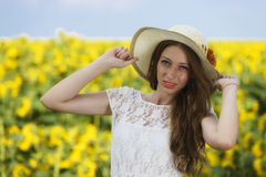 Young woman on blooming sunflower field Stock Images