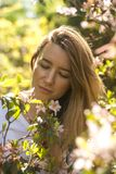 Young woman in blossoming bush in the sunny summer day stock images