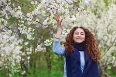 Young woman in the blossoming spring garden walks Stock Images
