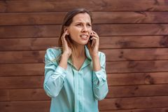 Young woman in blouse standing isolated on wall trying to hear caller on smartphone bad connection royalty free stock photos