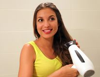 Young woman blow drying hair in bathroom.  stock image