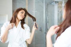 Young woman blow drying hair Stock Photos