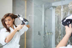 Young woman blow drying hair Stock Photos