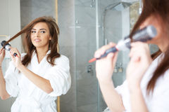 Young woman blow drying hair Stock Photo