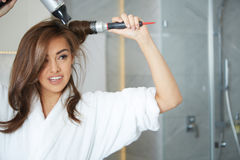 Young woman blow drying hair Royalty Free Stock Image