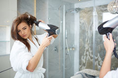 Young woman blow drying hair Stock Photography