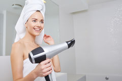 Young woman blow drying hair in bathroom. Young girl blow drying hair in bathroom stock photo