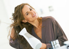 Young woman blow drying hair in bathroom. Happy young woman blow drying hair in bathroom stock photo